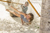 Дівчинка-підліток грає з маленьким братом в гамаку. — стокове фото