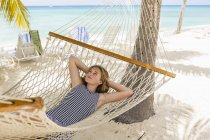 Teenage girl relaxing in hammock on tropical beach. — Stock Photo