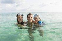 Mujer adulta que se encuentra en el agua del océano al atardecer con niños - foto de stock