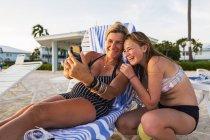 Мать и дочь делают селфи на пляже на закате, остров Гранд Кайман — стоковое фото