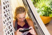 Блондинка в гамаке смотрит на смартфон . — стоковое фото