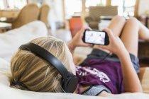 Вид сзади на девочку-подростка в наушниках и на экран смартфона — стоковое фото