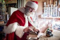 Man wearing Santa Claus costume standing in workshop and building wooden toy car. — Stock Photo