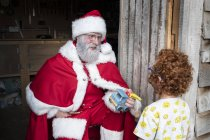 Man wearing Santa Claus costume giving wooden toy car to boy with red curly hair. — Stock Photo