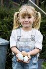 Menina loira de pé no jardim, segurando ovos frescos, sorrindo na câmera . — Fotografia de Stock