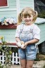 Menina loira de pé no jardim na frente da galinha, segurando ovos frescos . — Fotografia de Stock