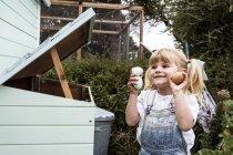 Menina sorridente de pé ao ar livre, segurando ovos recém-colocados nas mãos . — Fotografia de Stock