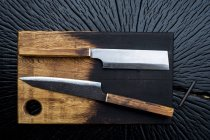 High angle close-up of two handmade knives on wooden cutting board. — Stock Photo