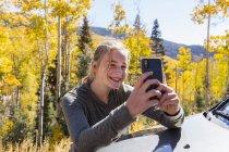 Девочка-подросток фотографируется со смартфоном, смотрит на осенние осины — стоковое фото
