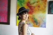 Японская женщина в шляпе стоит перед абстрактными картинами в художественной галерее . — стоковое фото