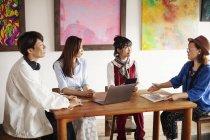 Grupo de homens e mulheres japoneses sentados na galeria de arte, realizando uma discussão . — Fotografia de Stock
