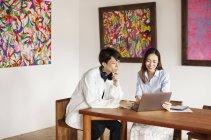 Japonês homem e mulher sentados em uma mesa em uma galeria de arte, olhando para o computador portátil . — Fotografia de Stock