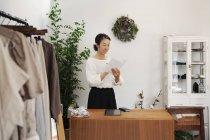 Японка, стоящая в маленьком модном бутике, читающая брошюру . — стоковое фото