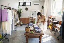 Japanerin steht in einer kleinen Modeboutique und betrachtet T-Shirts auf einem Couchtisch. — Stockfoto