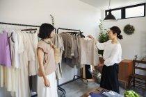 Zwei japanische Frauen, die in einer kleinen Modeboutique stehen und Tops betrachten. — Stockfoto