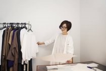 Japanese woman in glasses working at a desk in a small fashion boutique. — Stock Photo
