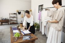 Two Japanese women standing in a small fashion boutique, arranging t-shirts on a coffee table. — Stock Photo