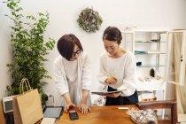 Due donne giapponesi in piedi in una piccola boutique di moda, guardando tablet digitale . — Foto stock
