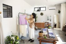 Japanese woman standing in a boutique, looking at clothes on a rail. — Stock Photo