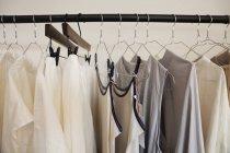 Primo piano di selezione di vestiti in colori naturali su una rotaia in una boutique . — Foto stock