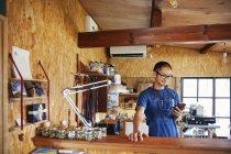 Японский мужчина в синем фартуке и очках стоит в кожаном магазине, используя мобильный телефон . — стоковое фото