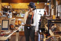 Japanese woman wearing hat and glasses browsing merchandise in a leather shop. — Stock Photo