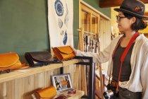 Japanerin mit Hut und Brille stöbert in einem Lederladen nach Waren. — Stockfoto