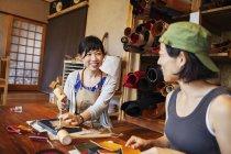 Due donne giapponesi sedute a un tavolo, che lavorano in un negozio di pelle . — Foto stock