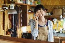 Lächelnde Japanerin mit Schürze steht in einem Lederladen und telefoniert. — Stockfoto