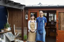 Japanese woman and man wearing aprons standing outside a leather shop, smiling in camera. — Stock Photo
