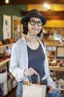 Donna giapponese che indossa cappello e occhiali in piedi in un negozio di pelle, tenendo la borsa della spesa, sorridente in macchina fotografica . — Foto stock