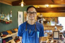 Japanese man wearing blue apron and glasses standing in a leather shop, smiling in camera. — Stock Photo