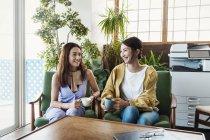 Deux professionnelles japonaises assises sur des chaises et discutant avec des tasses de boissons dans un espace de coworking, se souriant . — Photo de stock