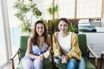 Две японки-профессионалки с чашками кофе сидят в коворкинге на стульях, улыбаясь в камеру . — стоковое фото