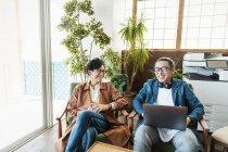 Два японских специалиста-мужчины работают над портативным компьютером в коворкинге . — стоковое фото