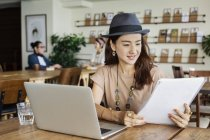 Японская женщина, работающая на ноутбуке в коворкинге, коллеги в фоновом режиме . — стоковое фото