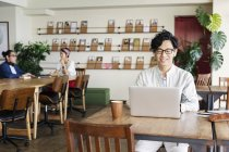 Японские бизнесмены, работающие за ноутбуком в коворкинг-пространстве . — стоковое фото
