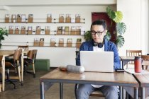 Japanischer Geschäftsmann sitzt an einem Tisch in einem Co-Working Space und benutzt einen Laptop. — Stockfoto