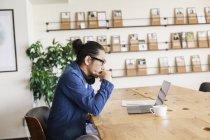 Professionista giapponese maschio seduto a un tavolo in uno spazio di co-working, utilizzando il computer portatile . — Foto stock