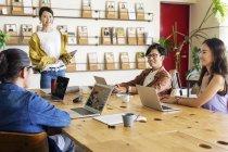 Gruppo di colleghi giapponesi di sesso maschile e femminile che lavorano su computer portatili in uno spazio di co-working . — Foto stock