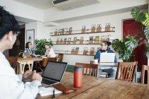 Японские бизнесмены, работающие на ноутбуках в коворкинг-пространстве . — стоковое фото