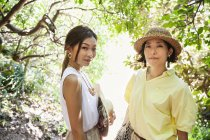 Two Japanese women wearing hats hiking in a forest. — Stock Photo