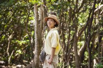 Japanese woman wearing hat hiking in a forest. — Stock Photo