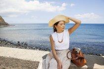 Japanerin mit Hut sitzt auf einer Mauer am Meer. — Stockfoto