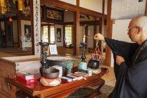 Sacerdote buddista inginocchiato nel tempio buddista, accende candele . — Foto stock