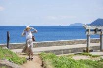 Japanerin mit Hut läuft am Meer entlang. — Stockfoto