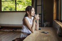Sorrindo japonesa sentada em uma mesa em um restaurante japonês, bebendo. — Fotografia de Stock
