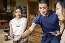 Kellner bedient zwei japanische Frauen, die an einem Tisch in einem japanischen Restaurant sitzen. — Stockfoto