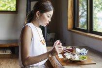 Mulher japonesa sentada em uma mesa em um restaurante japonês, comendo . — Fotografia de Stock
