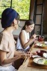 Deux Japonaises assises à une table dans un restaurant japonais, mangeant . — Photo de stock